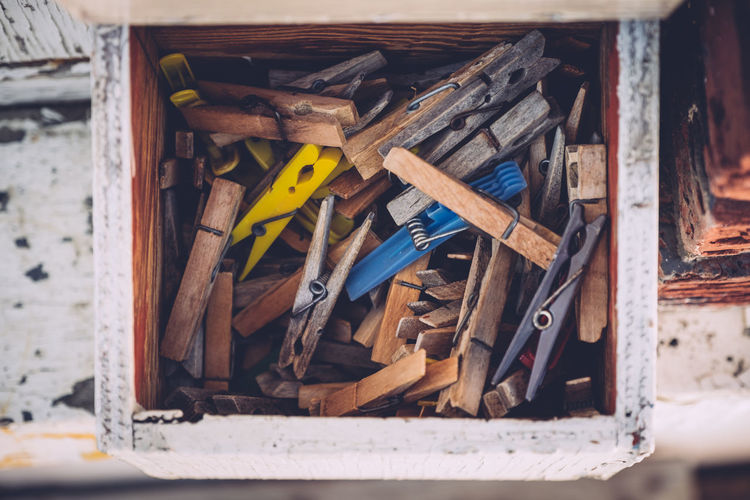 Close-up of clothespins in wooden container