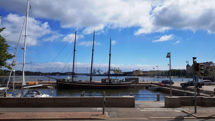 View of marina at harbor against cloudy sky