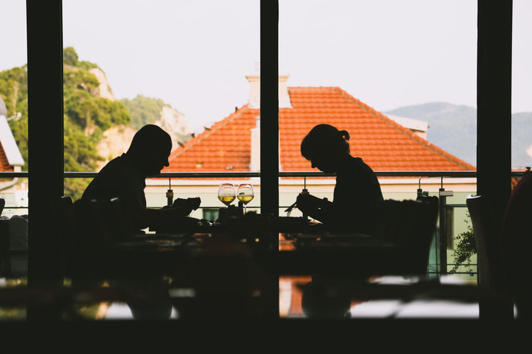 Silhouette people sitting at restaurant