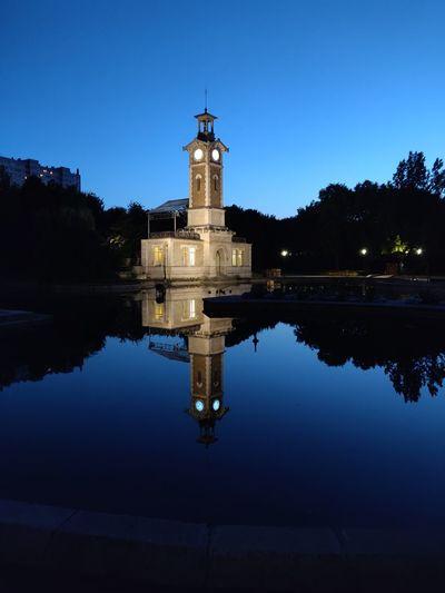 Reflection of illuminated building in lake at dusk