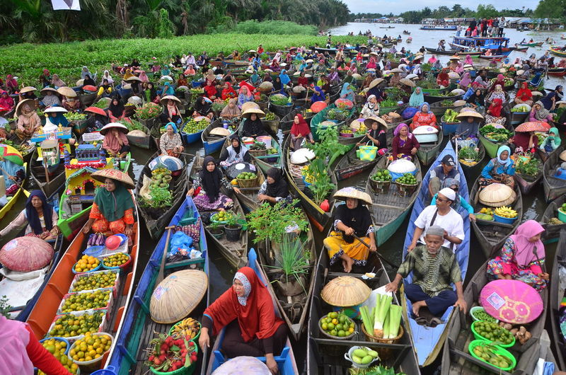 High angle view of people sitting on boats market stalls in lake