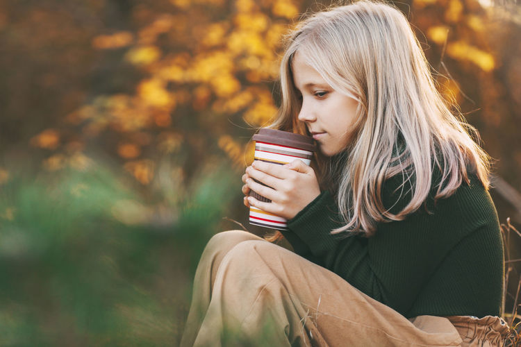 A beautiful teenage girl with blond hair sits thoughtfully in an autumn park, holds a thermos