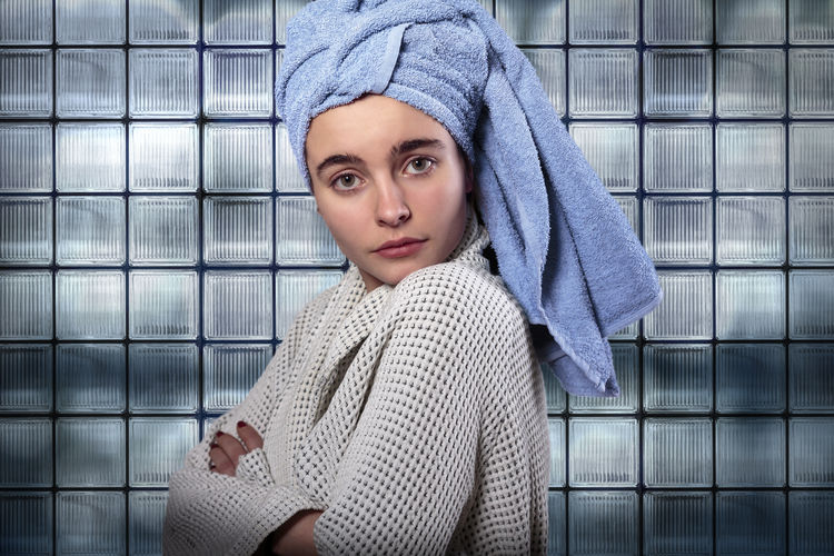 Portrait Of Woman Wearing Bathrobe Wrapped In Towel Standing Against Frosted Glass