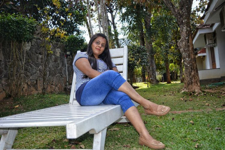 Portrait of woman sitting on lounge chair in yard