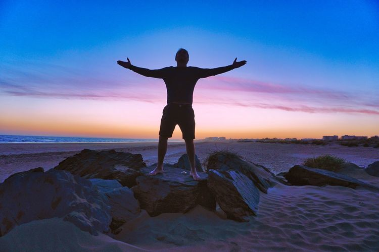 Rear view of man standing on rock at beach during sunset