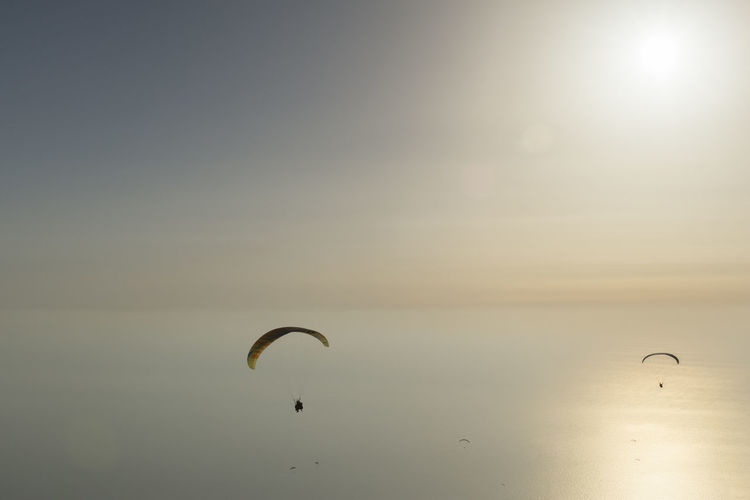 Kite flying over sea against sky during sunset