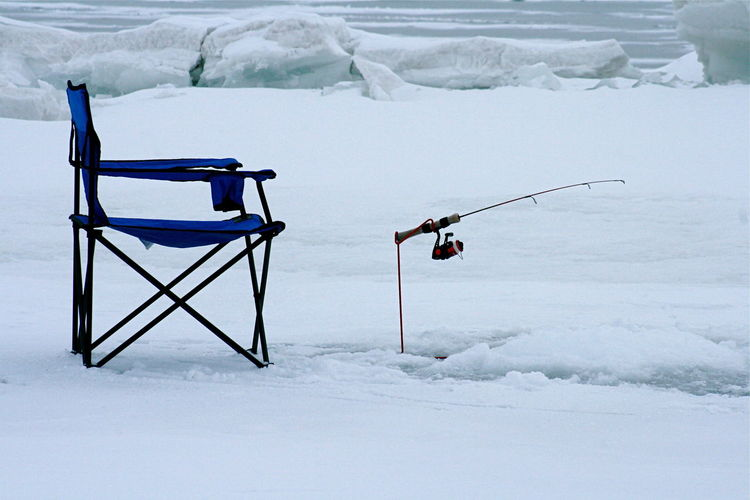 Empty foldable chair with fishing rod on snow