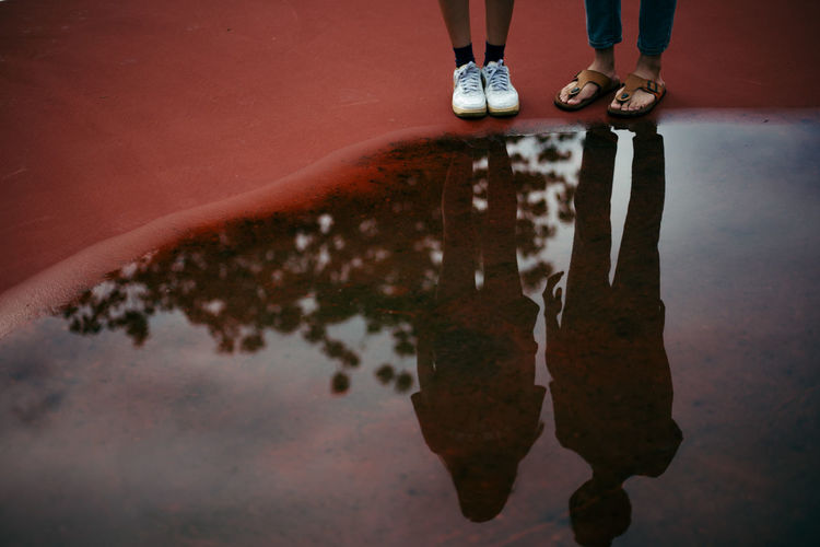 Low section of friends standing by puddle
