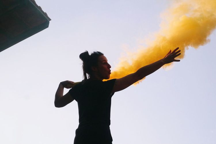 Young woman holding distress flare against clear sky