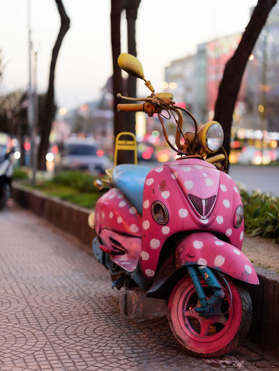 Close-up of pink motorcycle against blurred background