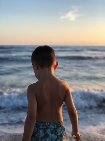 happy. EyeEm Selects Sea Water Beach Sky Land Rear View Real People Shirtless Nature Sunset Childhood Outdoors Child Horizon Over Water Boys Males  One Person Lifestyles