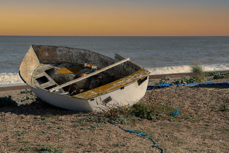 Abandoned boat moored on beach against sky during sunset