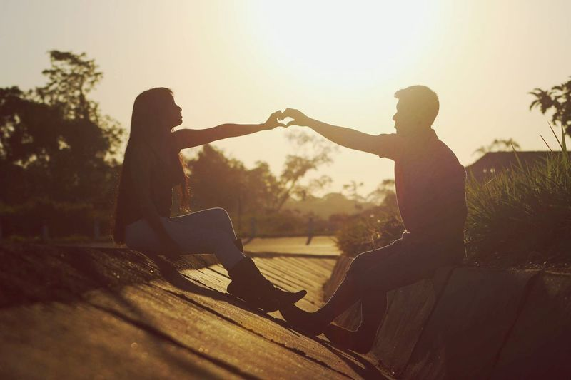 Midsection of couple sitting against sky during sunset