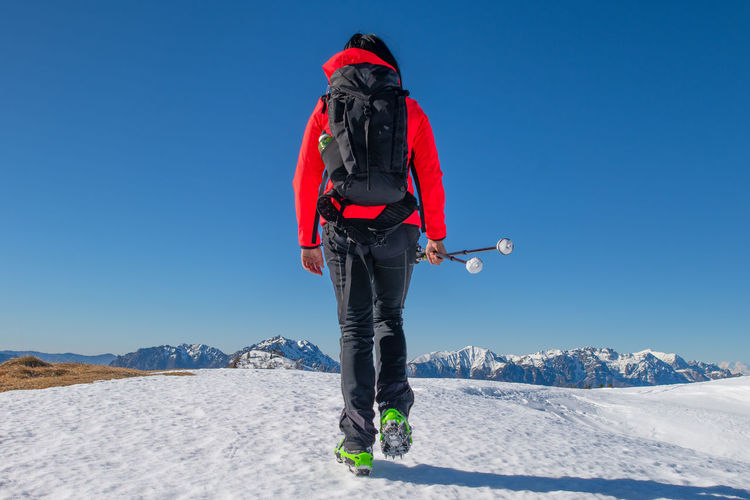 Rear view of woman on snowcapped mountain against clear sky