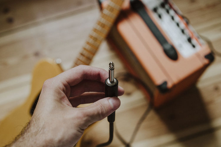 Cropped hand of person holding interconnect plug over guitar and equipment