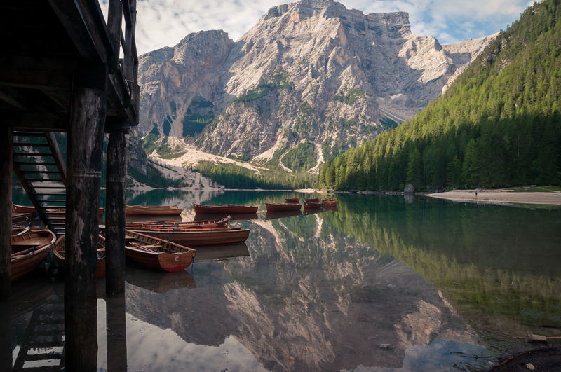 "Lake of Braies, Italy. View from the rafters of the stilt house. Rowing boats moored. Reflection of the ""Croda del Becco"" mountain and the forest on the water Mountain Water Reflection Beauty In Nature Mountain Range Lake Scenics - Nature Tranquility Tranquil Scene Nature Mode Of Transportation Day Transportation Tree Waterfront Idyllic No People Travel Destinations Formation"