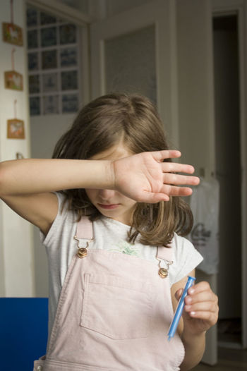 Girl Covering Eyes With Hand At Home