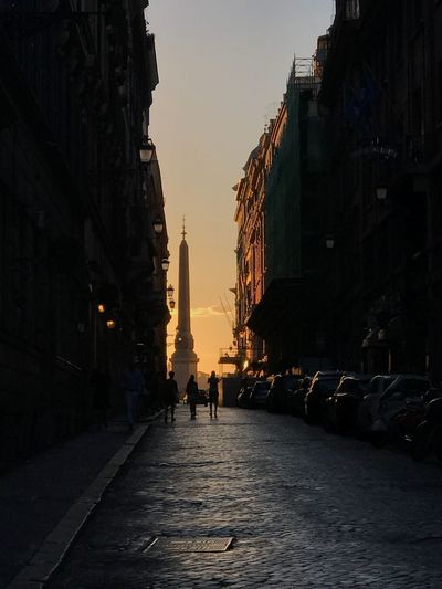 People Walking On Street Amidst Buildings During Sunset