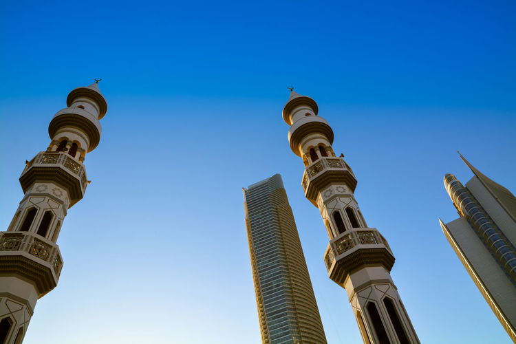 Low angle view of minarets and skyscrapers against clear blue sky