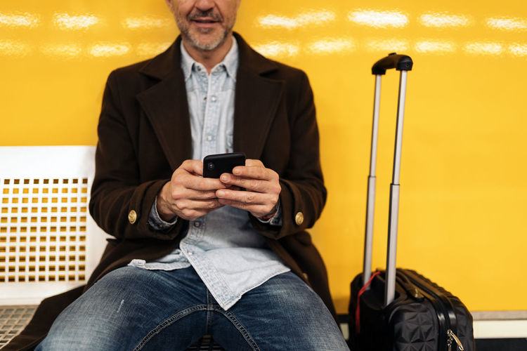 Full length of man using mobile phone