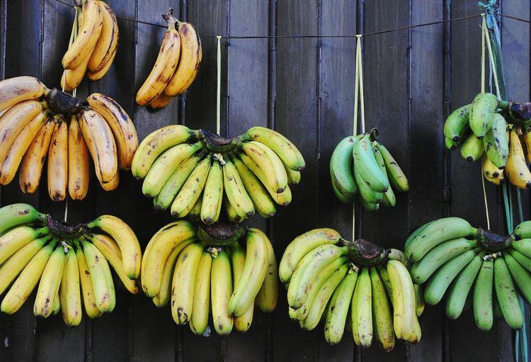 Bananas Hanging Against Fence For Sale At Market