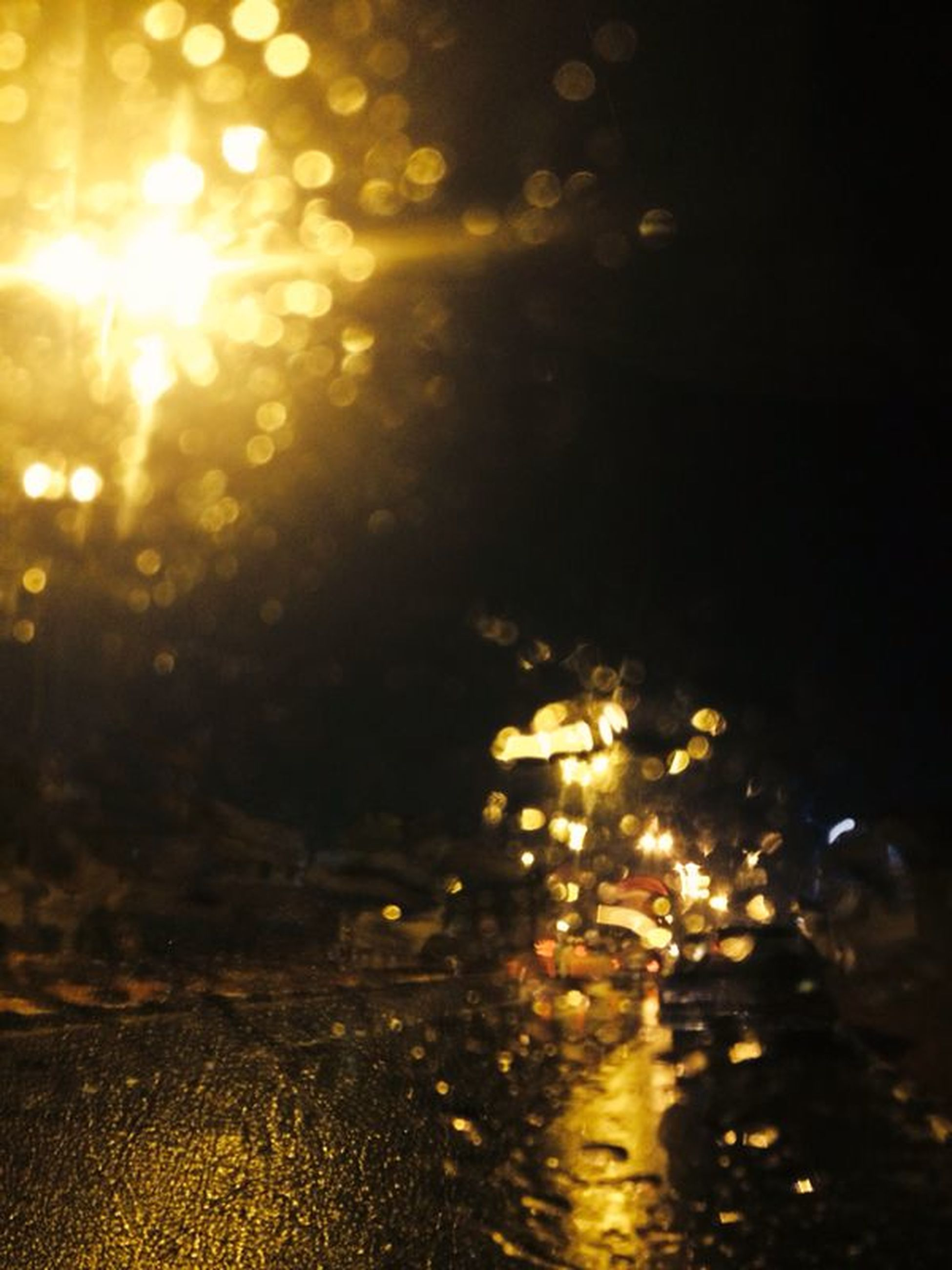 illuminated, night, street, street light, glowing, lighting equipment, lens flare, wet, transportation, light - natural phenomenon, defocused, road, car, no people, land vehicle, water, focus on foreground, glass - material, outdoors, reflection