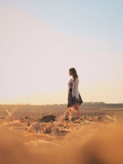 Beautiful Woman Walking On Agricultural Field Against Sky