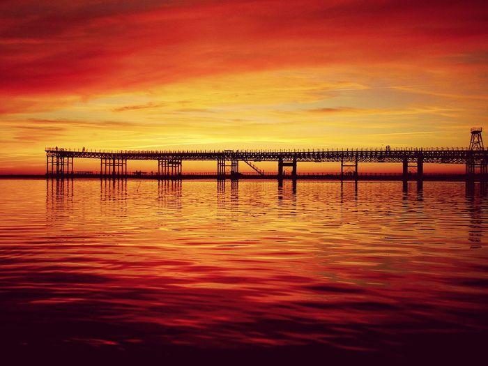 Silhouette pier by river against orange sky