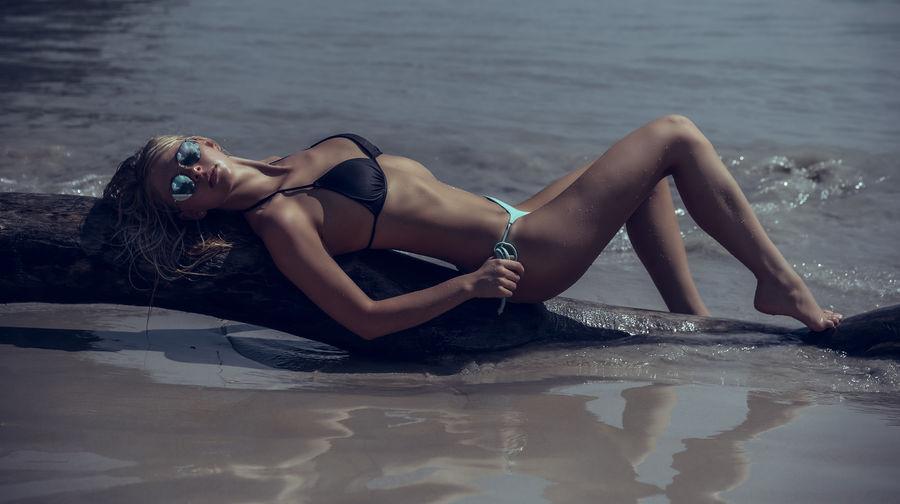 Woman in bikini lying on fallen tree trunk at beach