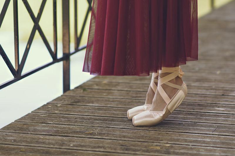 Low section of ballet dance standing on footbridge