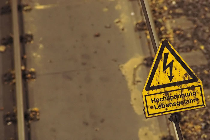 Close-up Communication Day Focus On Foreground High Voltage Sign Information Information Sign Metal No People Non-western Script Protection Safety Script Security Sign Text Triangle Shape Warning Sign Warning Symbol Western Script Yellow