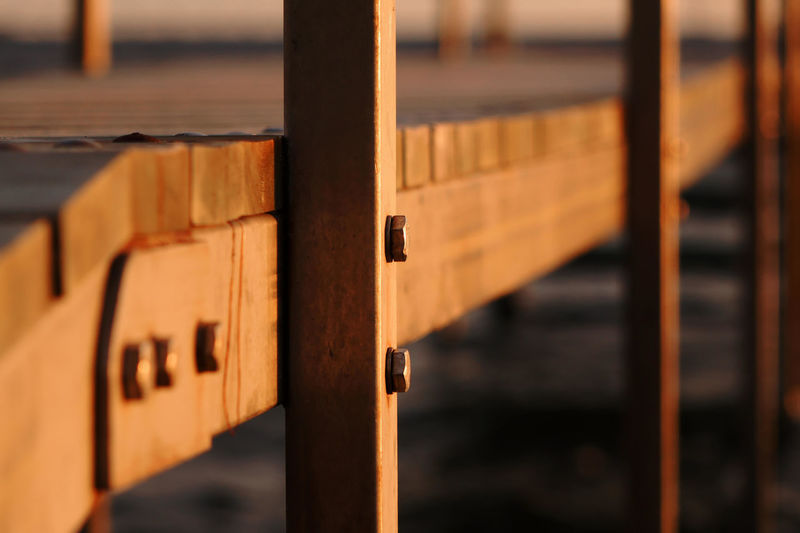 Close-Up Of Wooden Pier At Beach During Sunset