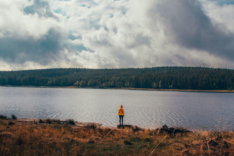 Rear view of man standing by lake against sky