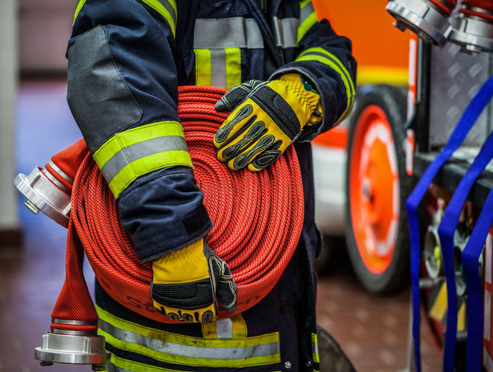 Firefighter carry a fire hose to the fire engine Action Active Activity Alarm Carry Coiled Emergency Fire Fire Brigade Fire Department Fire Engine Firefighter Fireman Fireproof Hand HDR Hose Man Mission People Rolled Up Use Used Vehicle Water