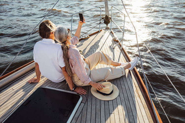 Rear view of people sitting on sailboat in sea