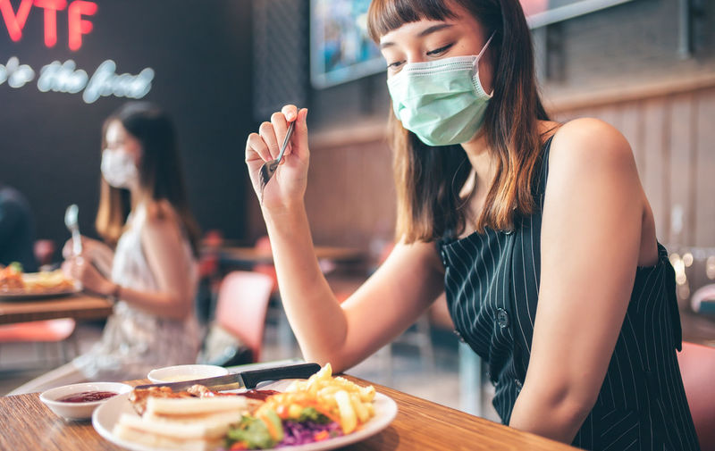 Midsection of woman having food at restaurant