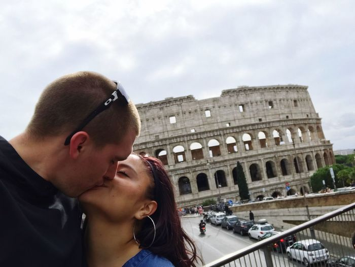 Close-up of couple kissing against coliseum