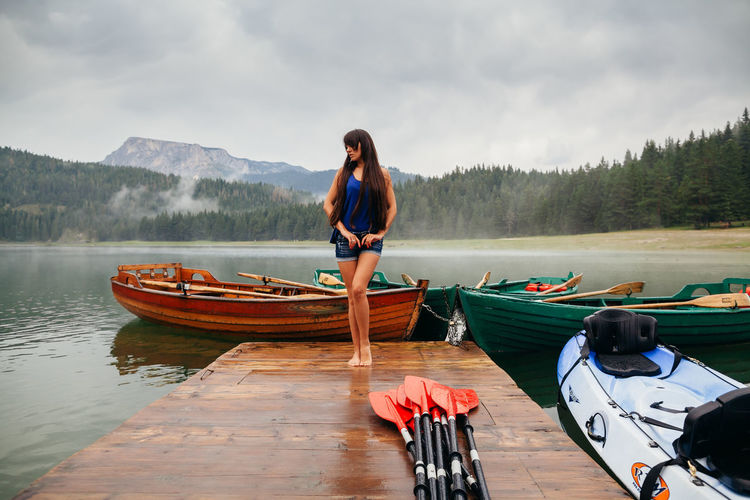 Woman travel on kayak and boat with lake and mountains view in Montenegro EyeEm Best Shots Travel Vacations Adult Beautiful Woman Beauty In Nature Boats Casual Clothing Day Durmitor Kayak Lake Leisure Activity Lifestyles Mode Of Transportation Montenegro Mountain Nautical Vessel One Person Outdoors Real People Standing Transportation Water Young Adult