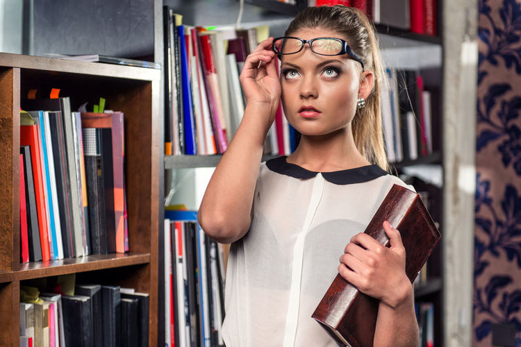 Woman Looking Up While Holding Book At Library