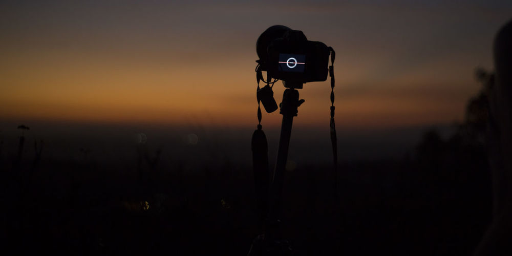 Silhouette of camera on field against sky during sunset