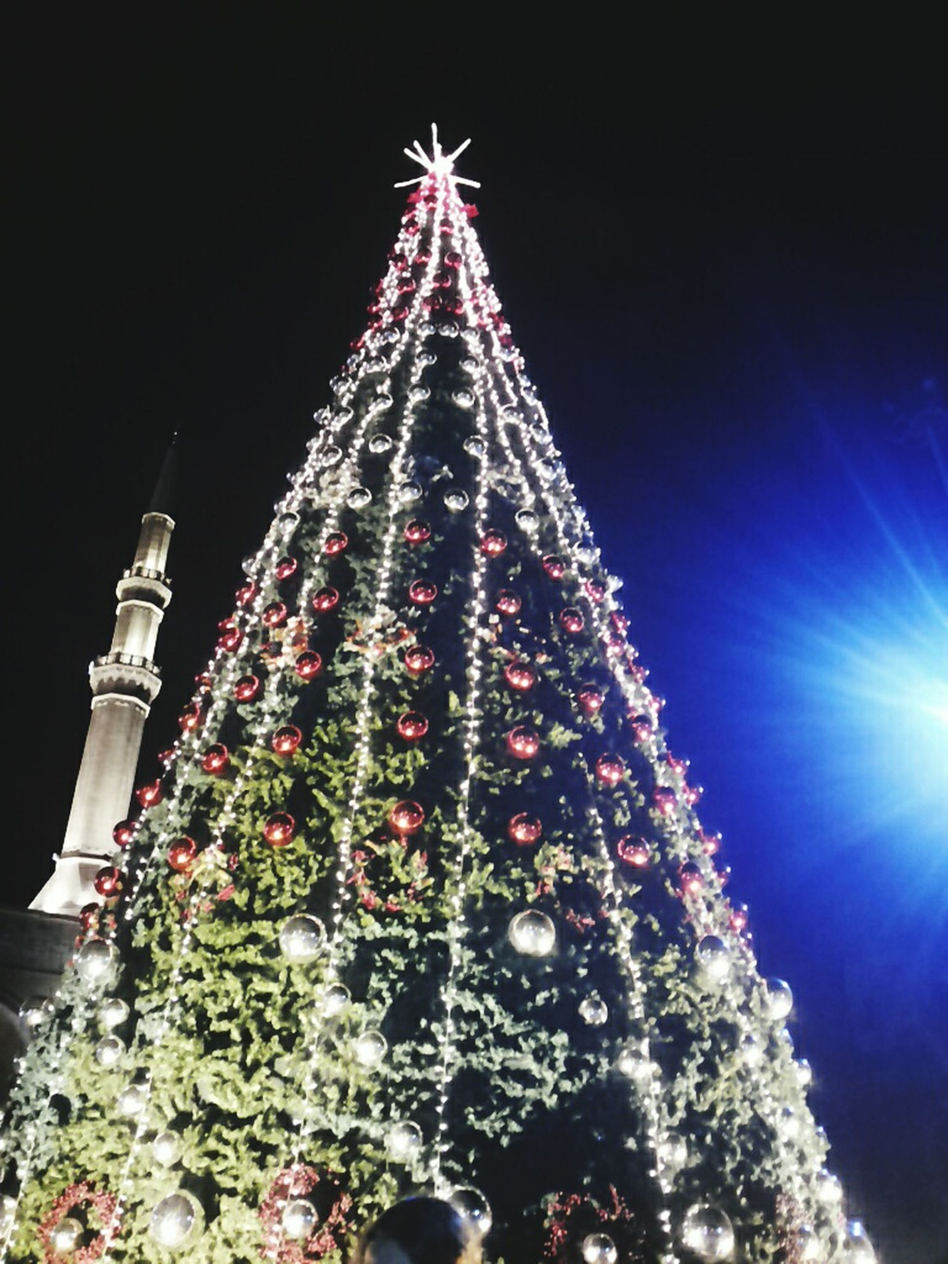 illuminated, low angle view, night, celebration, tradition, christmas, cultures, large group of people, christmas tree, decoration, clear sky, sky, lifestyles, christmas decoration, leisure activity, outdoors, christmas lights, religion, men