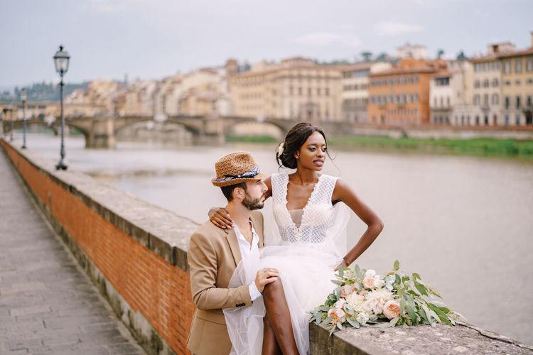 Couple holding umbrella on bridge against buildings