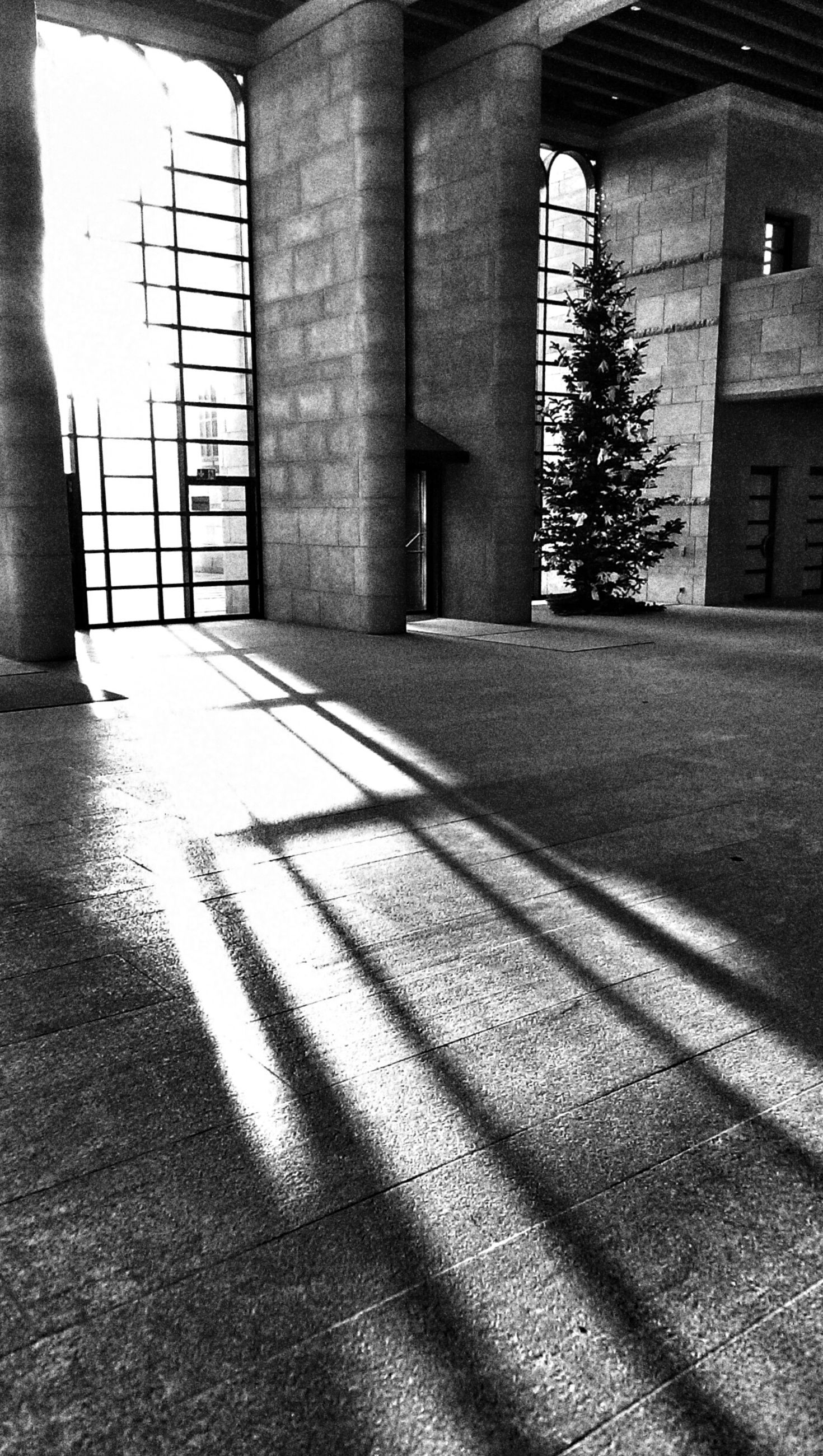 architecture, built structure, building exterior, shadow, sunlight, building, window, street, day, architectural column, city, the way forward, door, wall - building feature, no people, outdoors, cobblestone, walkway, empty, history