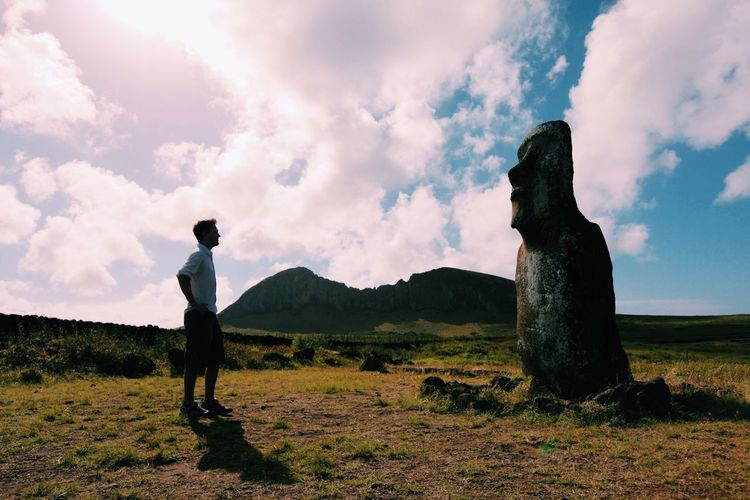 Man Standing In Front Of Moai Statue On Field Against Sky At Easter Island