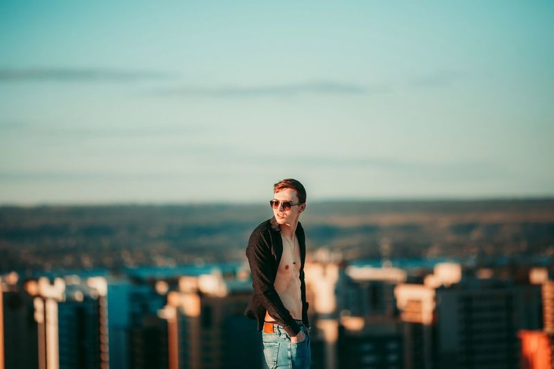 Portrait of young man wearing sunglasses standing against cityscape