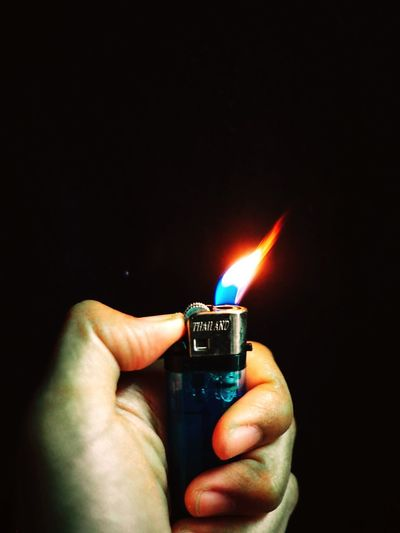 Close-up of hand holding burning candle against black background