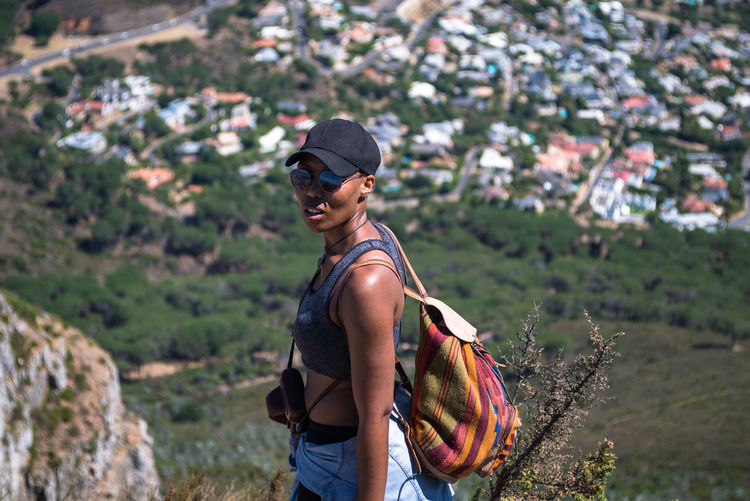 Portrait of woman in sunglasses standing on hill