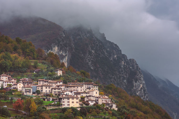 Buildings in mountains against sky