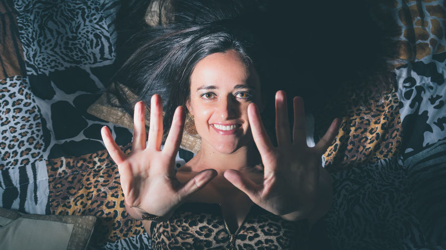 High angle portrait of woman gesturing while lying on bed