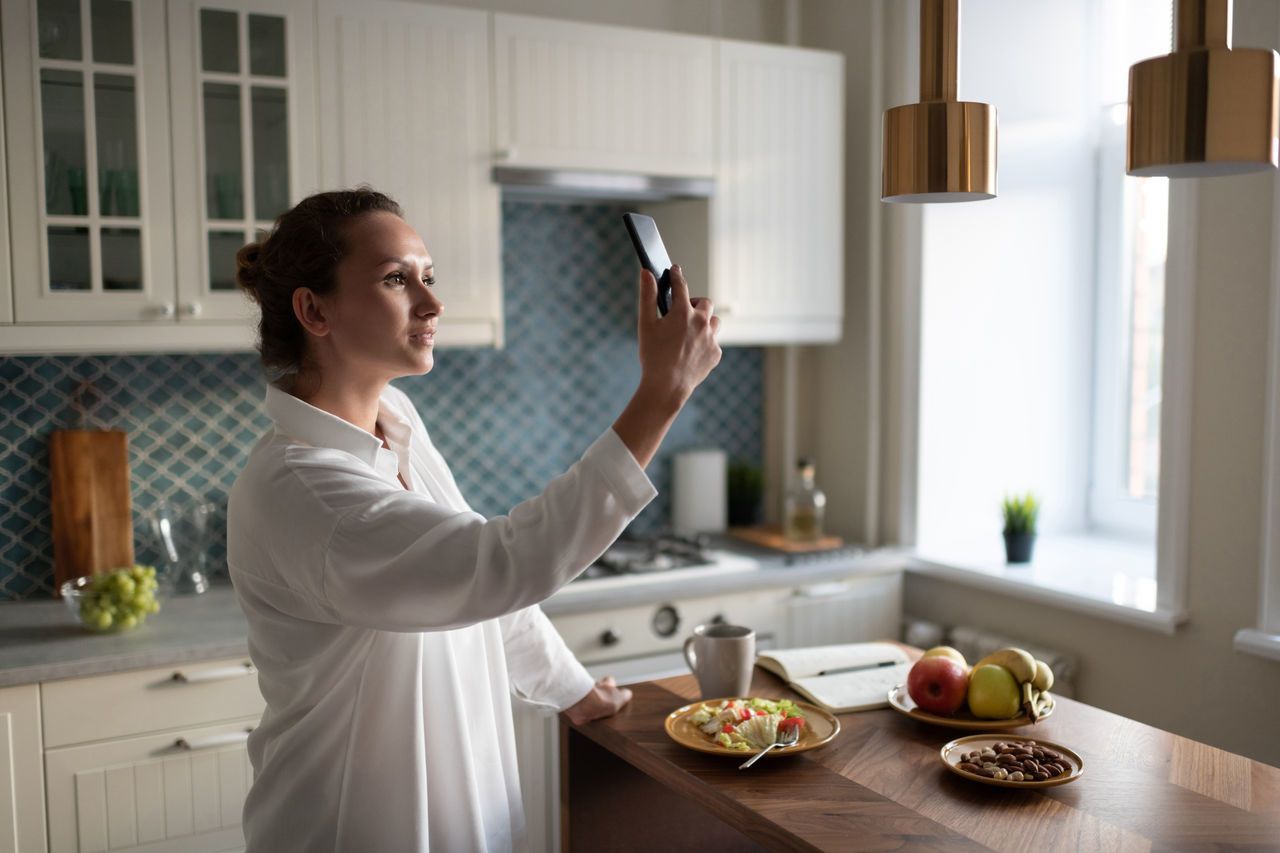 WOMAN STANDING BY FOOD AT HOME